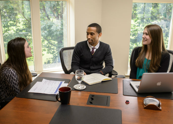 A group of young professionals meet at a conference table.