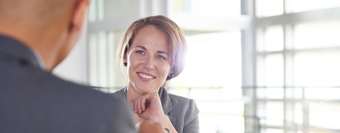 A woman meets with a customer in a sunny conference room.