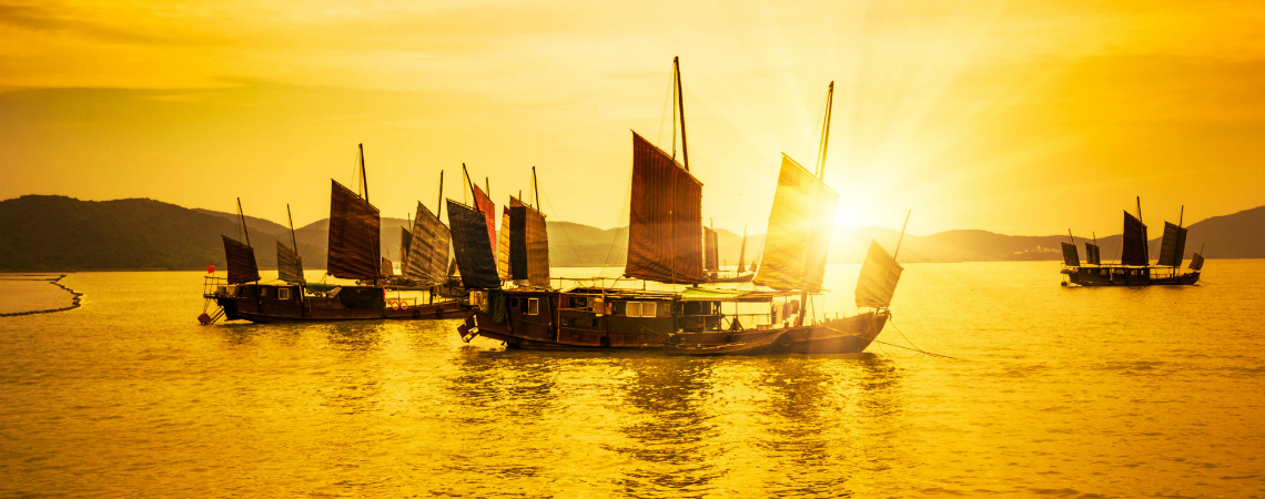 As the sun sets, Chinese junks are moored in a sheltered harbor.