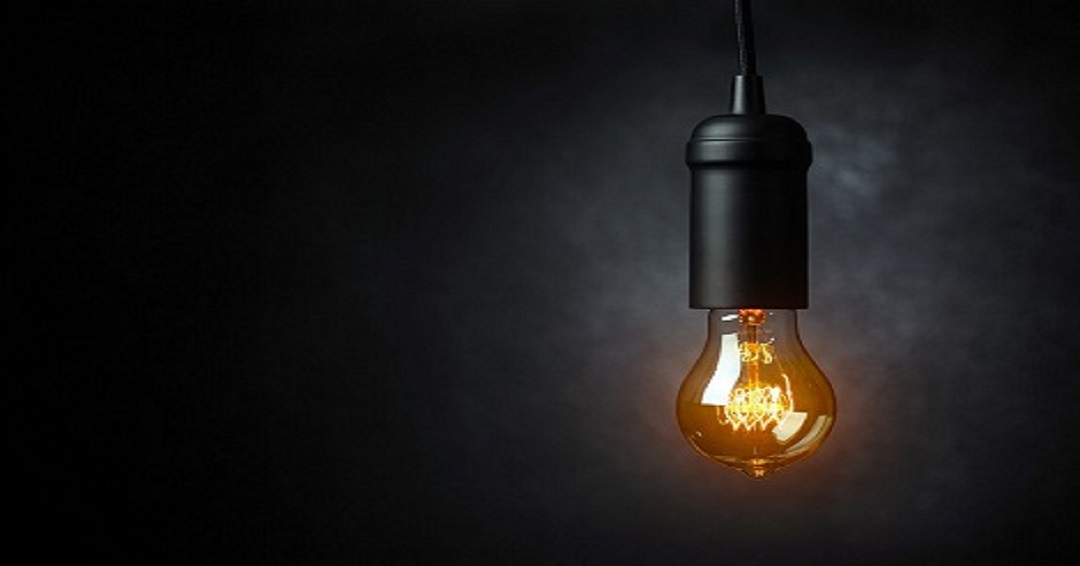 A bare incandescent lightbulb shines in front of a dark gray background.