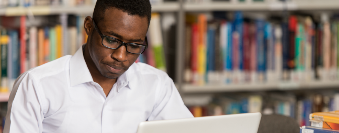 A young man wearing glasses works on a laptop in a library.