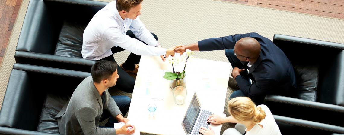 An aerial view of a four-person team of professionals collaborating in an informal meeting space.