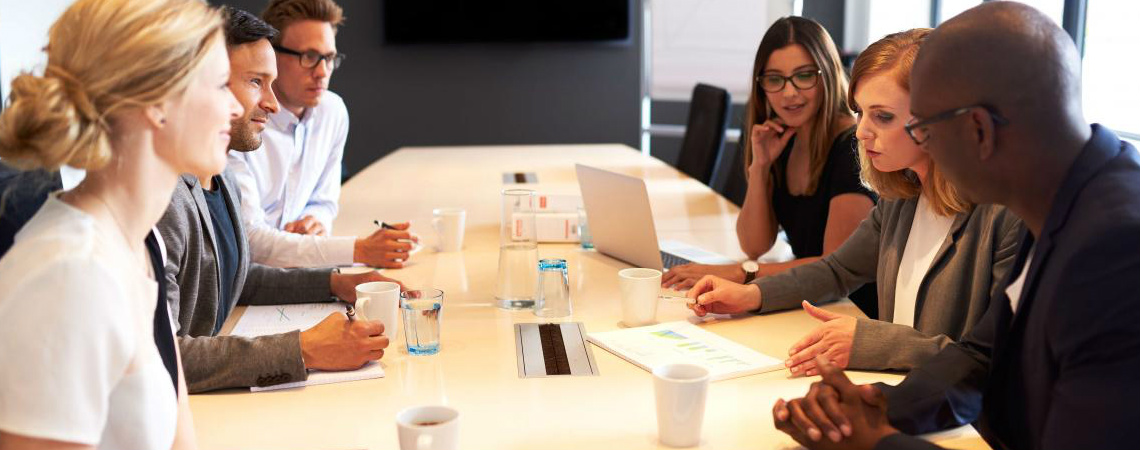 A mixed group of young professionals gather to collaborate around a conference table.