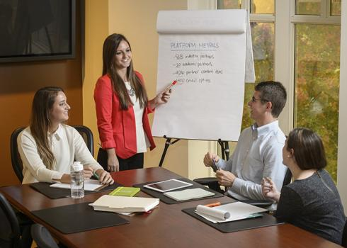 A group of young professionals gather around a conference table to listen to a flip-chart presentation.