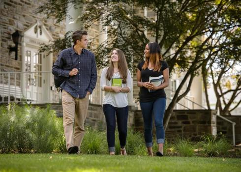 Three college students walk across the quad, away from an academic building.