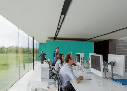 Employees sit at workstations along a long table in a sleek, modern office full of windows and natural light.