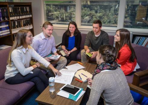 Gathered around a small table in the library, a group of college students study together.