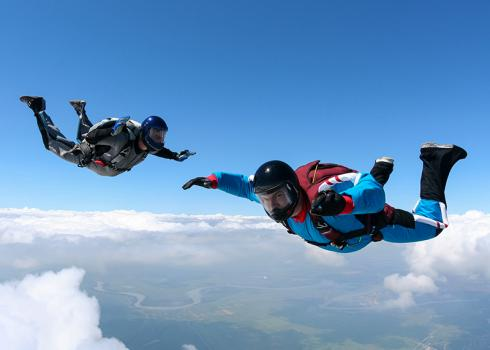 A pair of skydivers during freefall above the clouds. A river meanders in the distance.