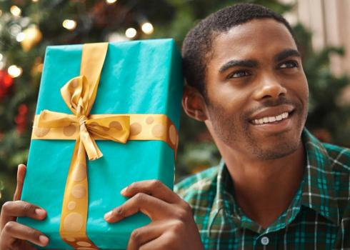 A young man shakes a wrapped present, listening to guess what's inside.