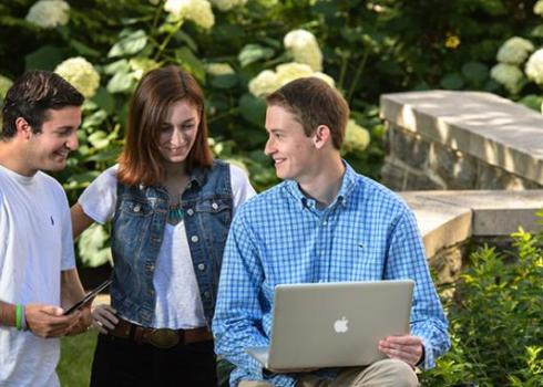 Three college students gather around a laptop while hydrangeas bloom in the background.