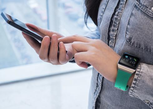 A woman wearing an Apple watch taps the smartphone in her other hand
