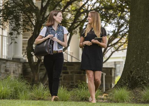 Two college women walk away from an academic building near a mature tree.
