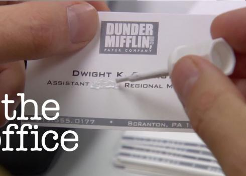 In a screeshot from The Office, Dwight uses white-out to alter his business cards.
