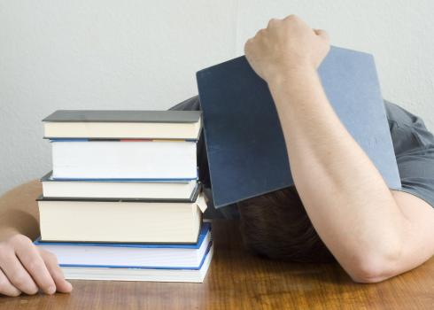 Beside a stack of books, an overwhelmed student hides his head...and maybe catches 40 winks.
