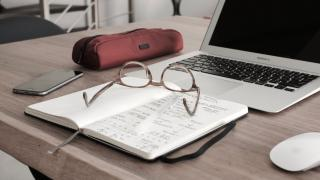 Glasses on notebook in front of laptop