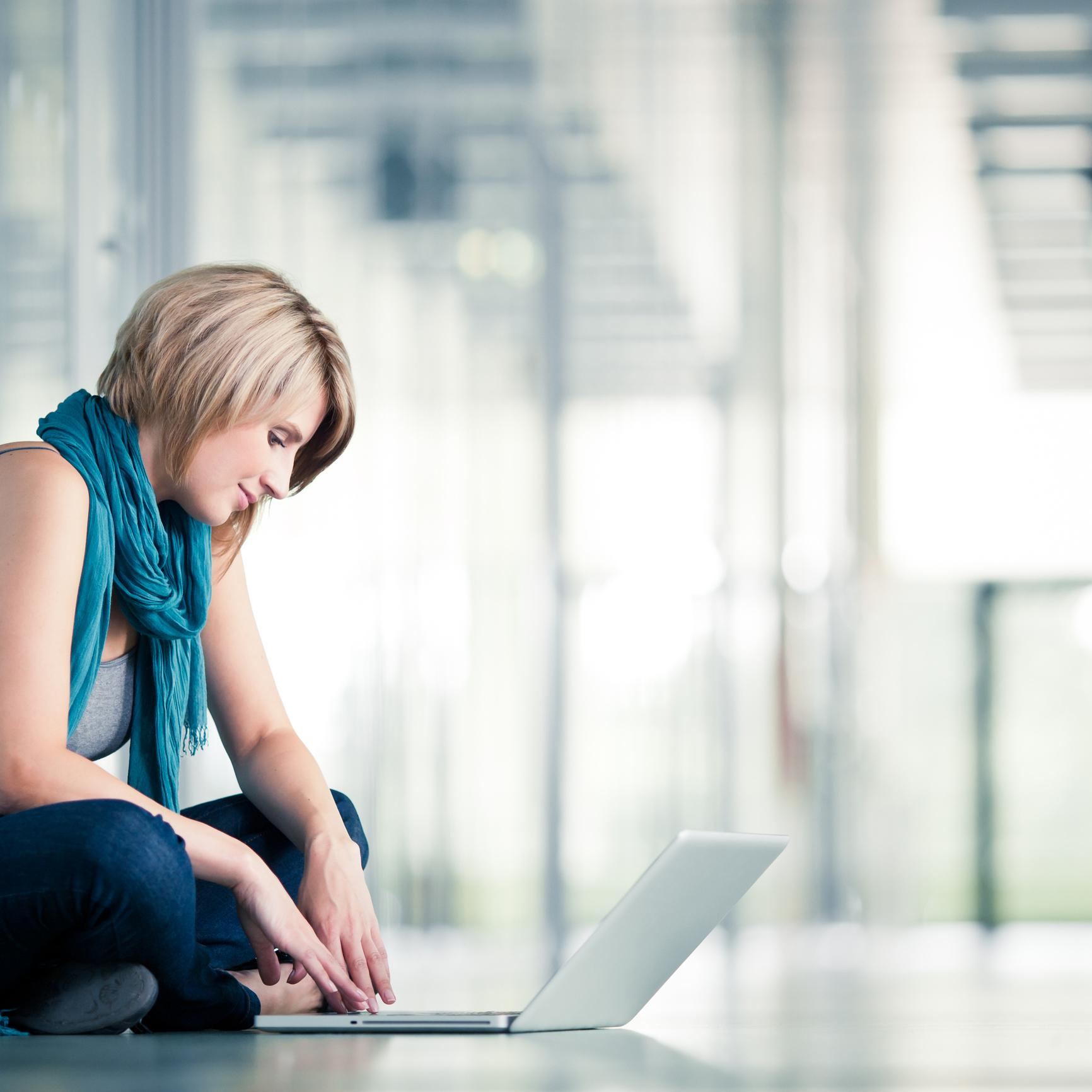 In a sunny hallway, a student sits on the floor using her laptop.