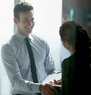A young man shakes hands with a woman in a business setting.